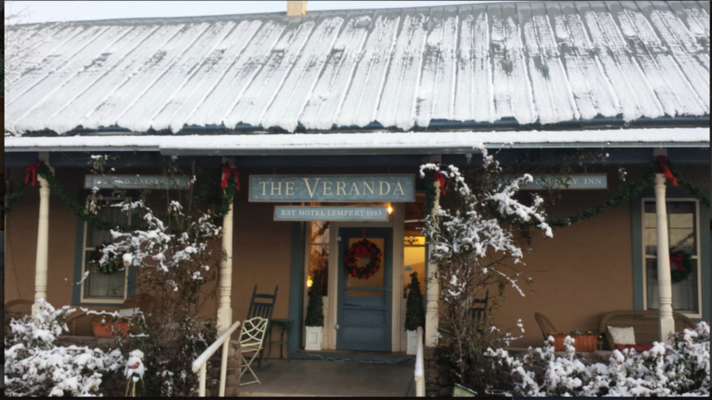A person standing in front of a building at The Veranda Historic Inn.