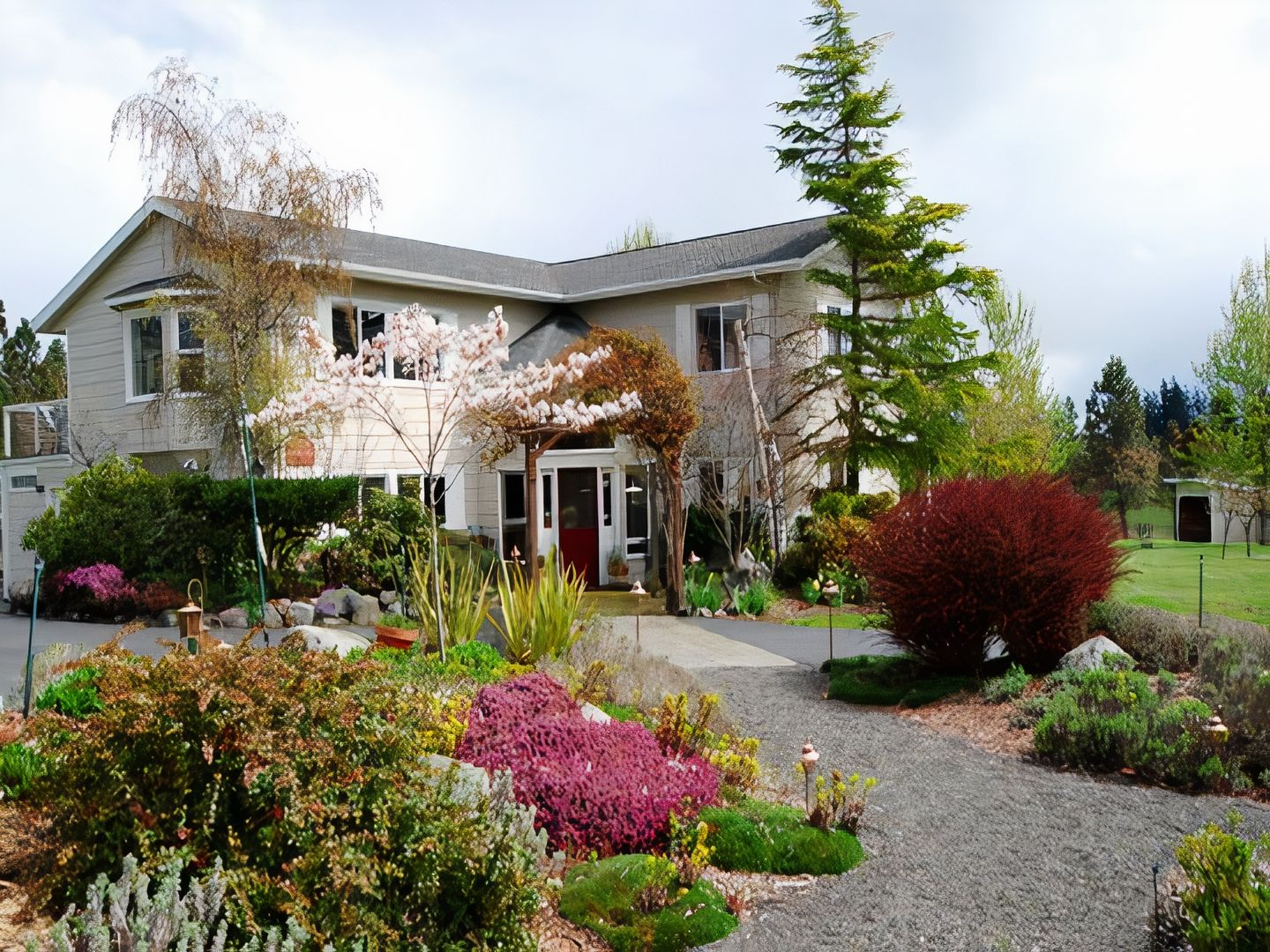 A close up of a flower garden in front of a house at Trumpeter Inn.