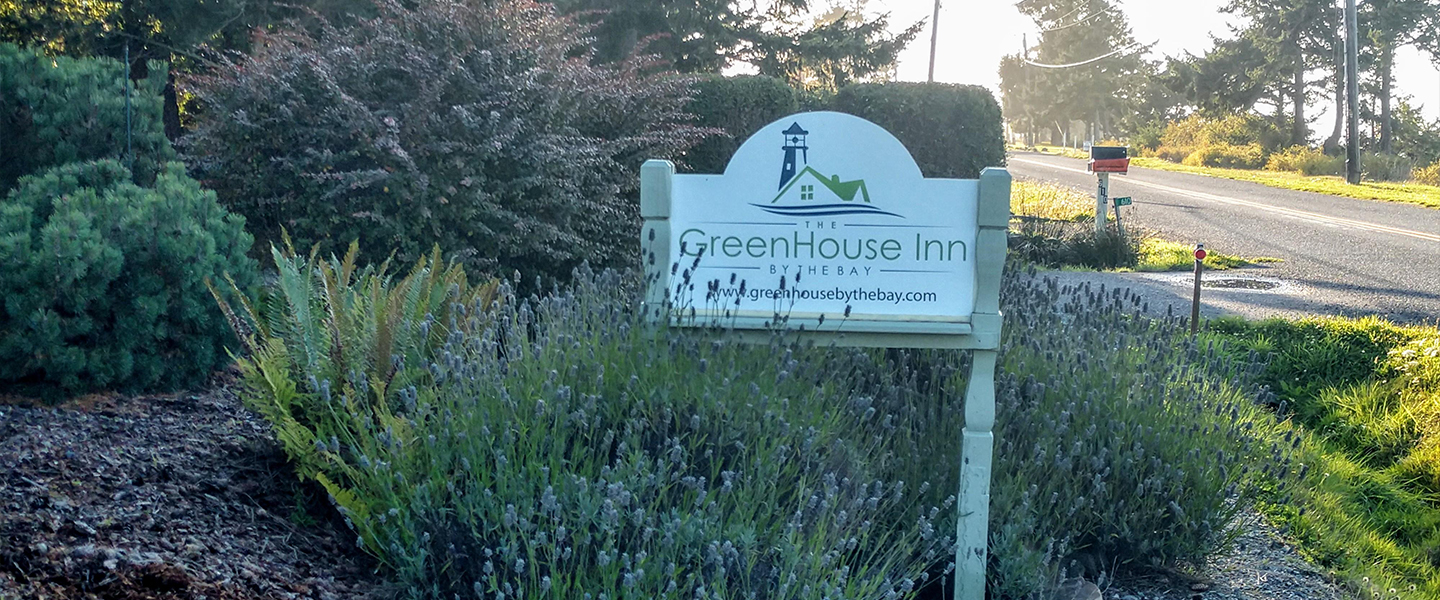 A sign on the side of a road at GreenHouse Inn by the Bay.