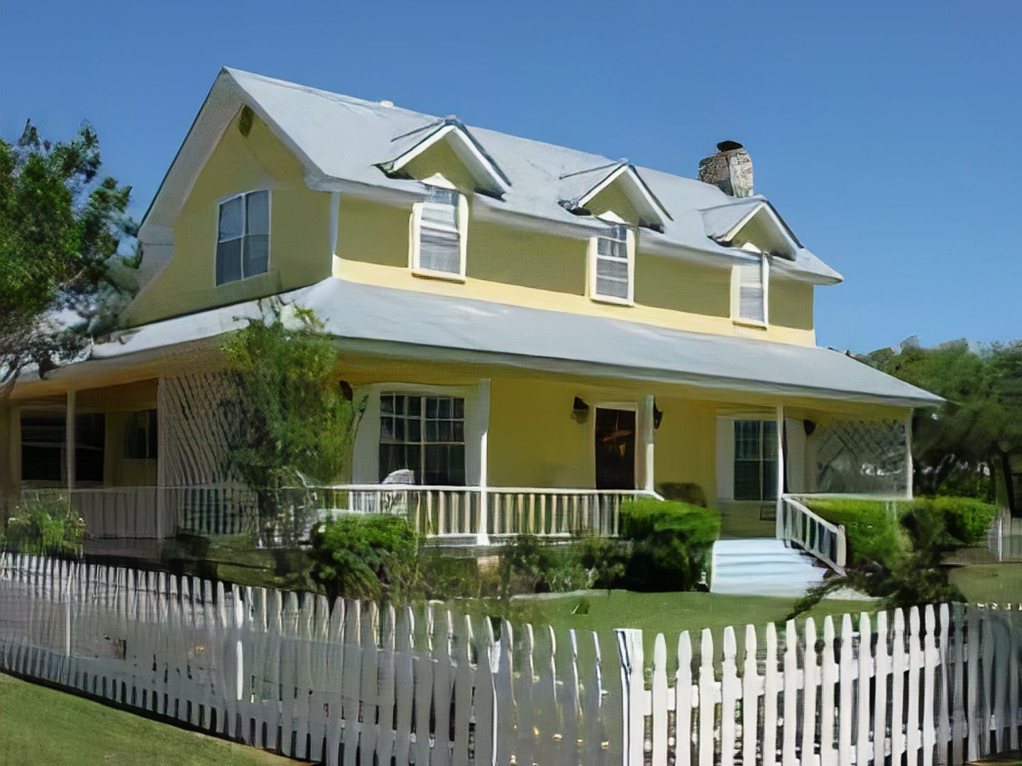 A house with a lawn in front of a building at Yellow House Bed and Breakfast.