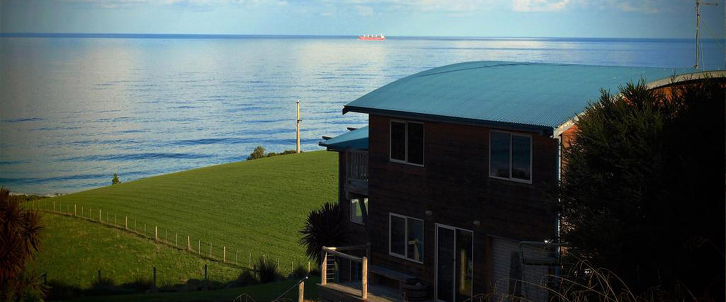 A large body of water in front of a house at Castaways Apollo Bay.