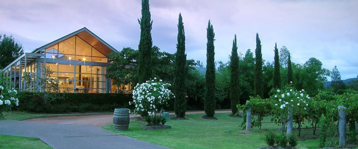 A house with trees in the background at  Hunter Valley Cooperage B & B.