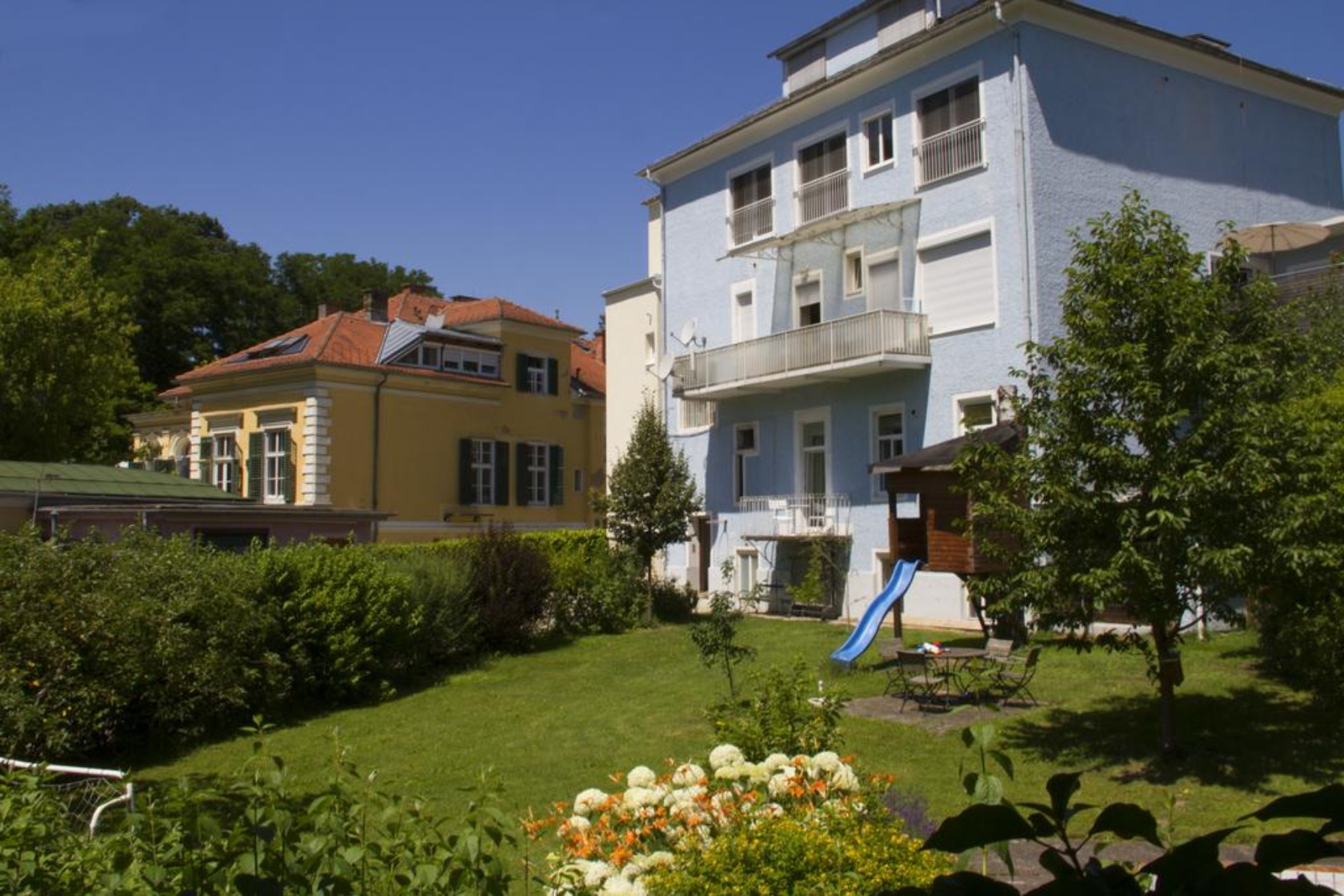 A large lawn in front of a house at Hotel Villa Rückert.