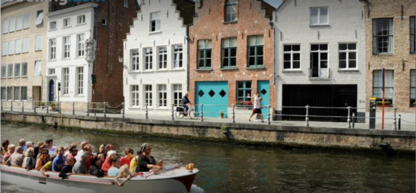 A group of people on a boat in front of a building at B&B Huyze Walburga.