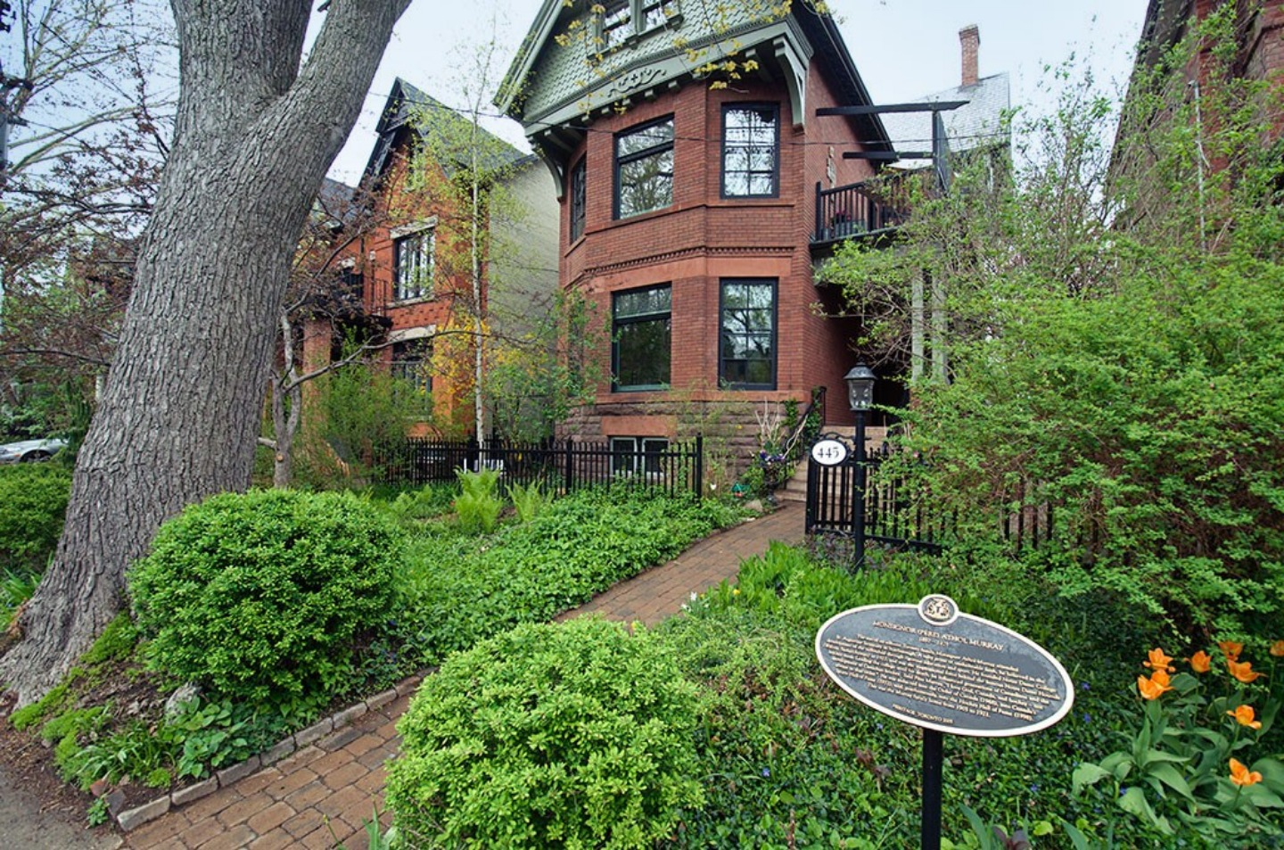 A large brick building with grass and trees at Annex Garden Bed & Breakfast and Suites.
