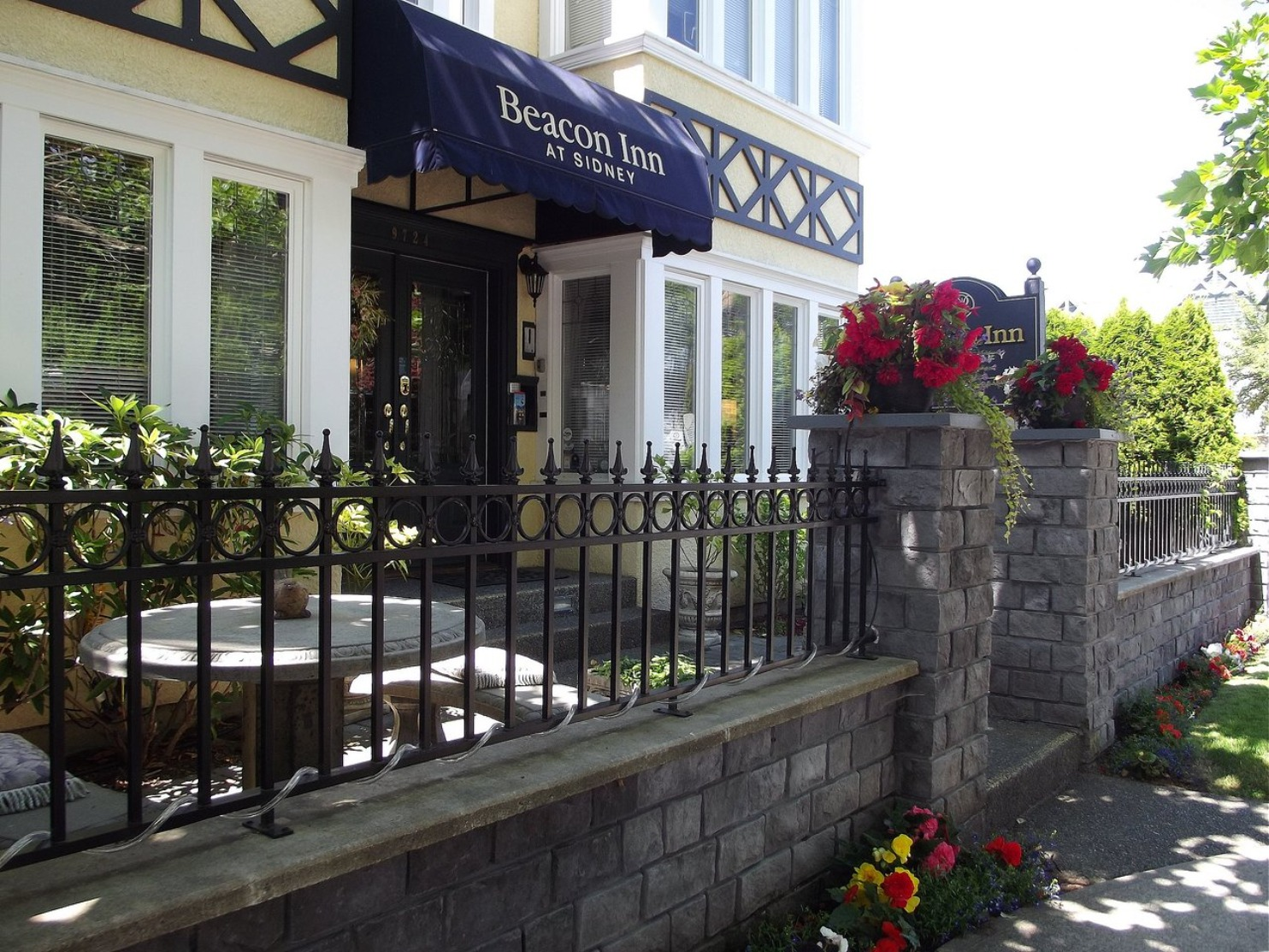 A vase of flowers sits in front of a building at  Beacon Inn at Sidney.