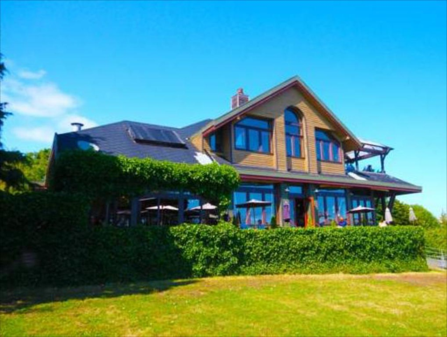 A house with trees in the background at Spinnakers Gastro Brewpub & GuestHouses.
