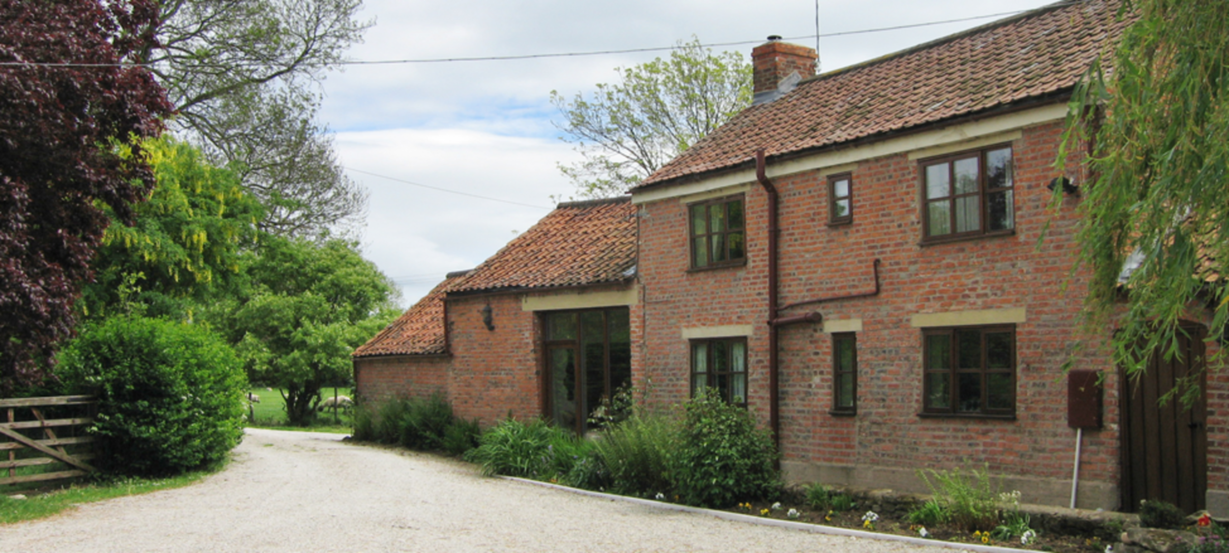 A large brick building with grass in front of a house at Brickfields Farm.