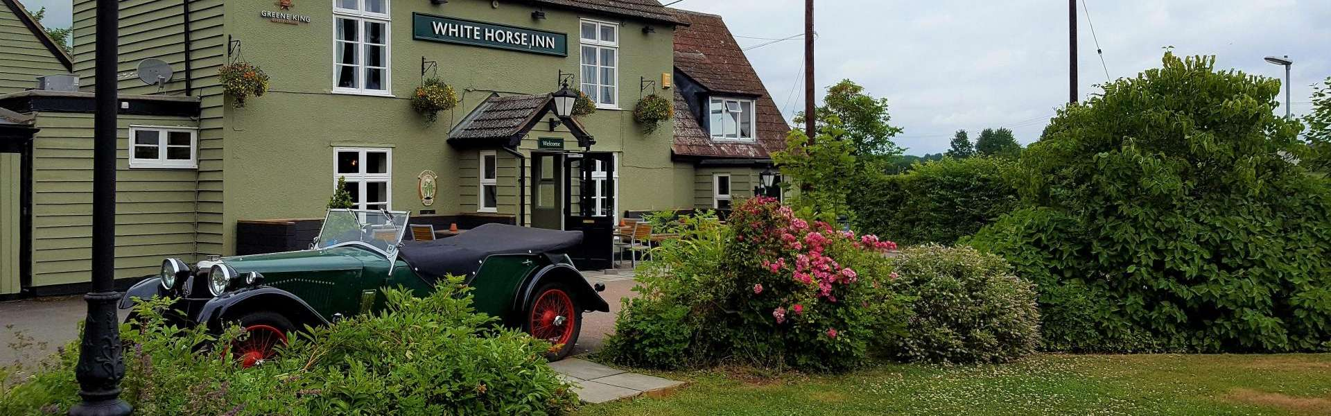 A car parked in front of a house at The White Horse Inn.