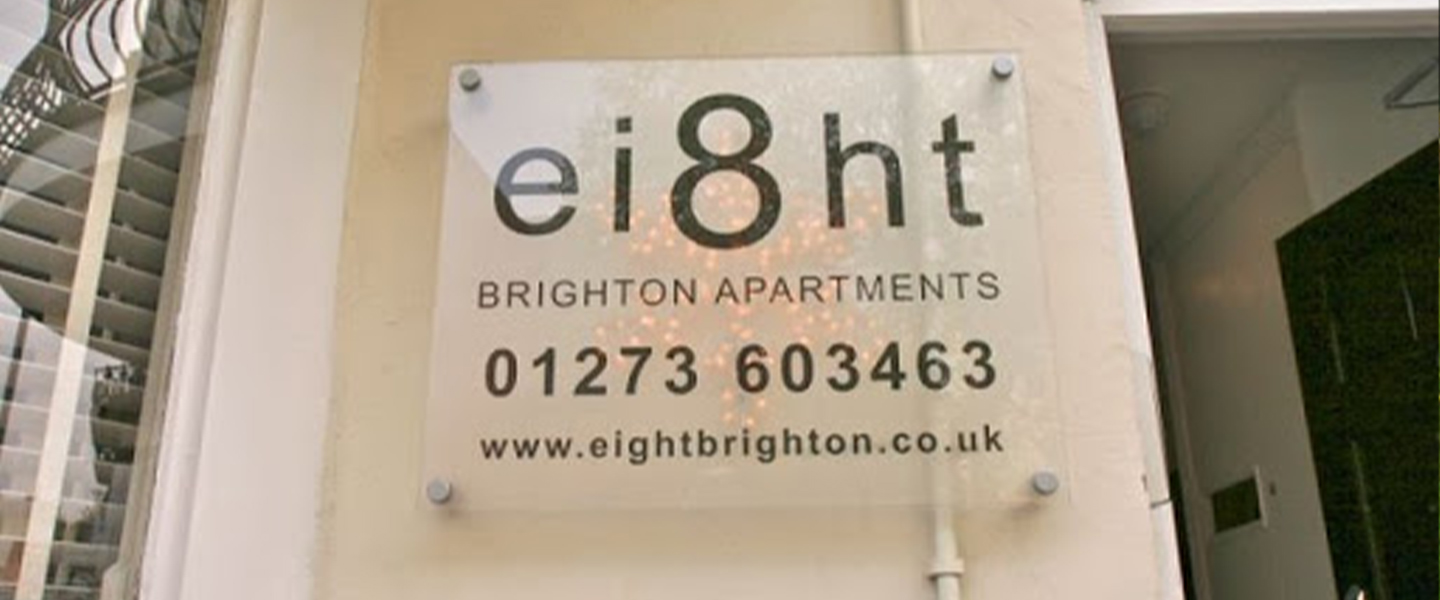 A close up of a sign at EI8HT Brighton Apartments.