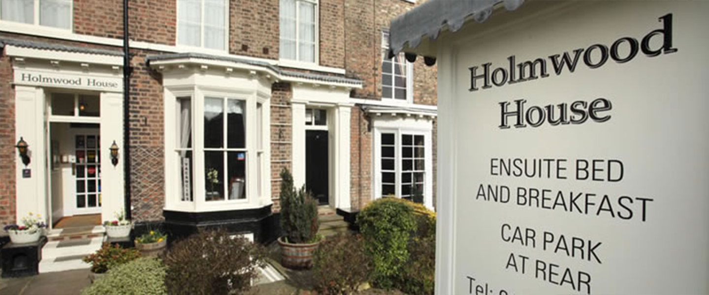 A sign in front of a house at Holmwood House Hotel.