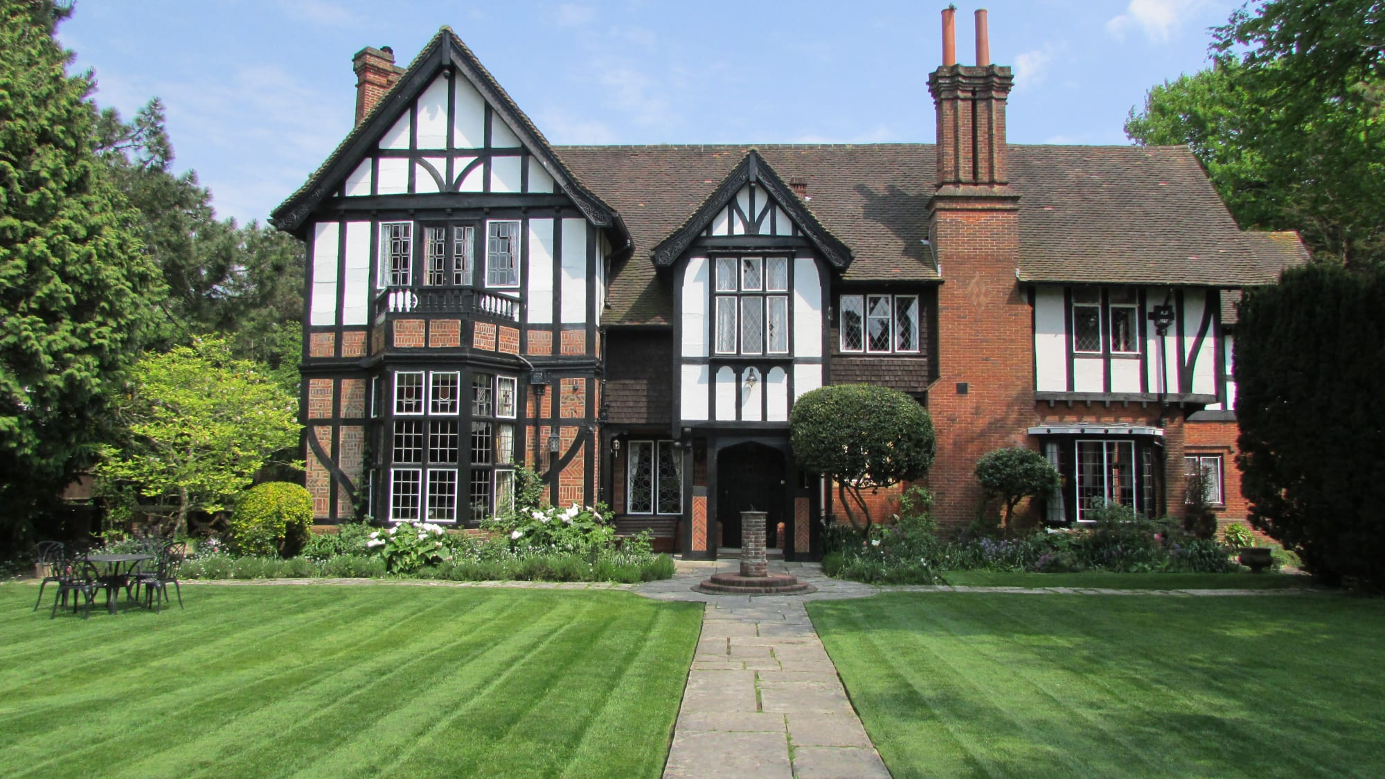 A large brick building with grass in front of a house at Tudor Grange Hotel.