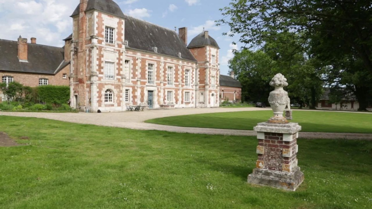 A large lawn in front of a building at  Chateau Lardier.