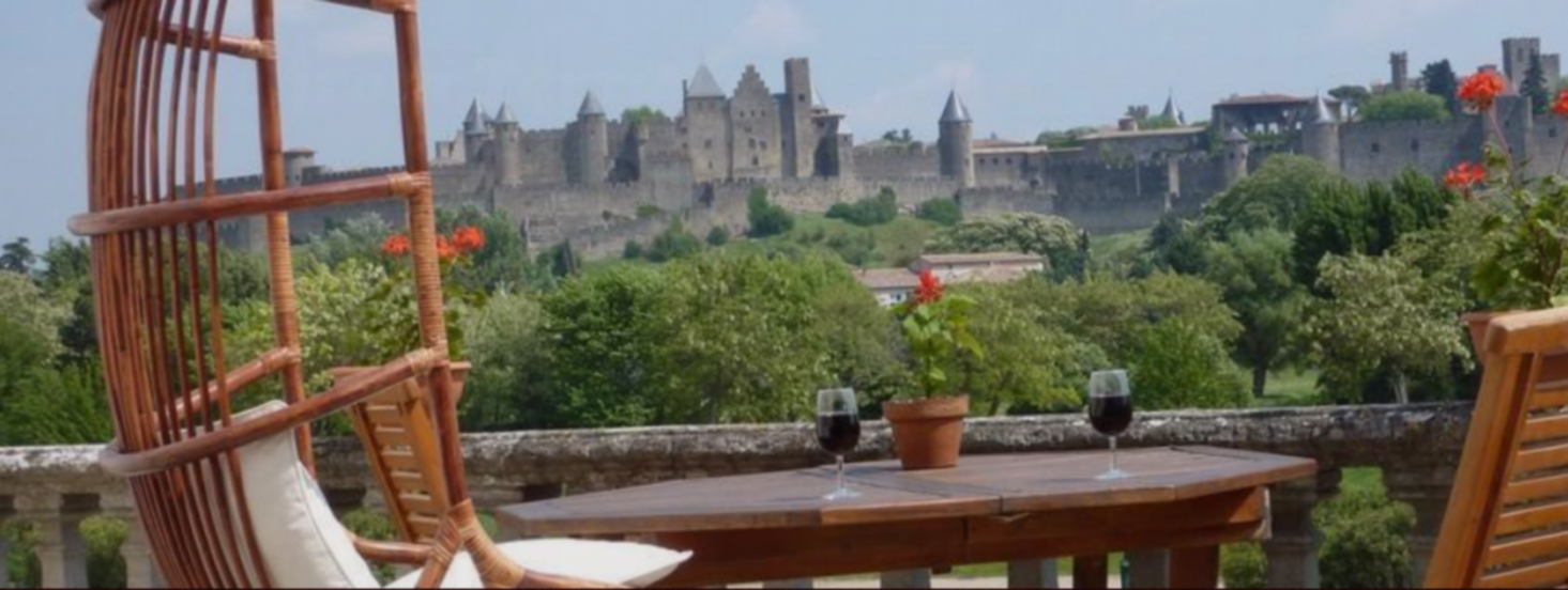 A chair sitting in front of a building at Carcassonne Guest House.