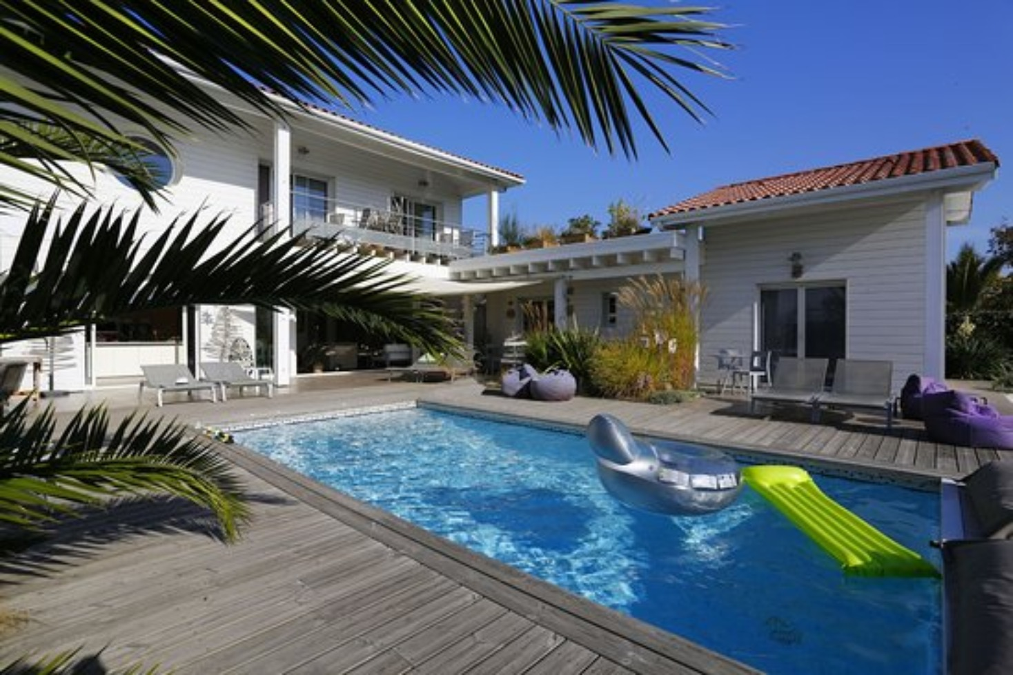 A house with a pool in front of a building at Côte & Dune.