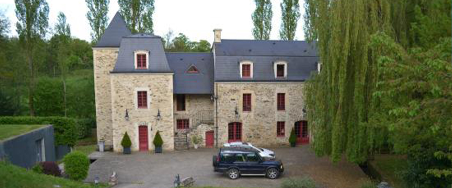 A car parked in front of a house at Le Moulin d'Ajon.
