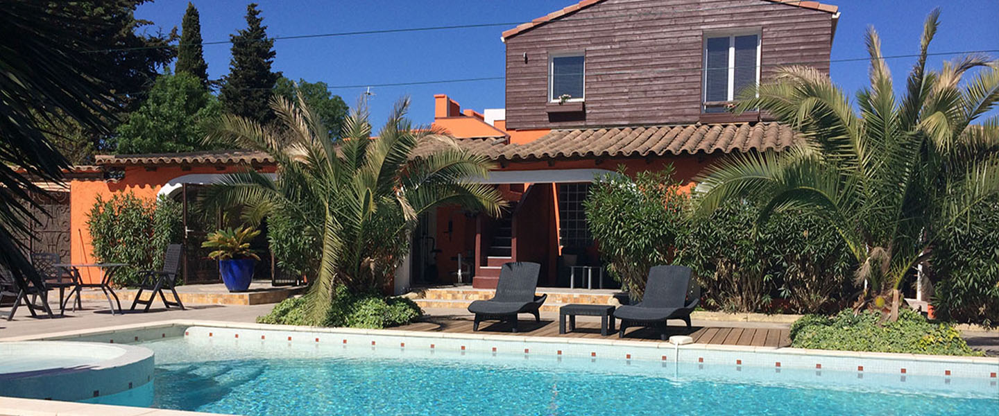 A pool in front of a building at Le Patio 34.
