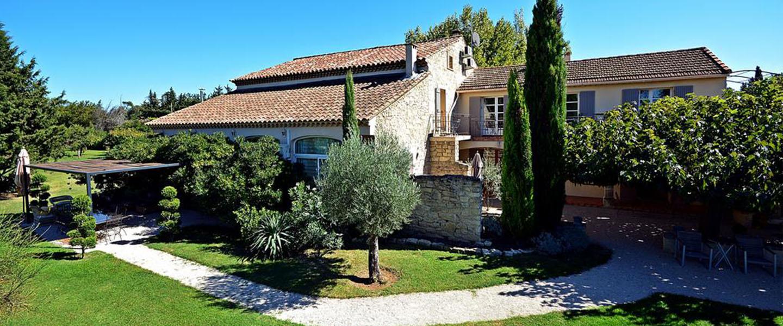 A large lawn in front of a house at Le Mas les Fleurs d'Hilaire.