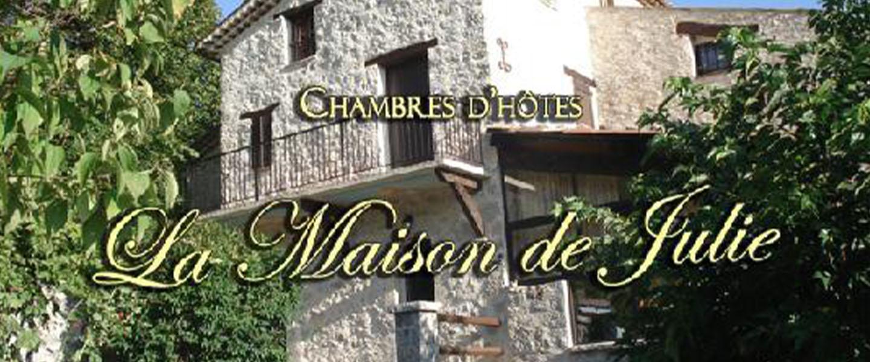 A sign in front of a brick building at La Maison de Julie.