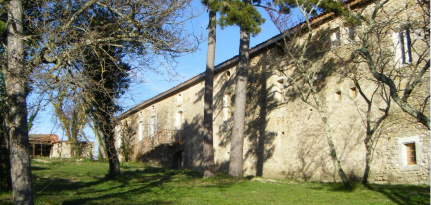 A tree in front of a brick building at La Chadenède.