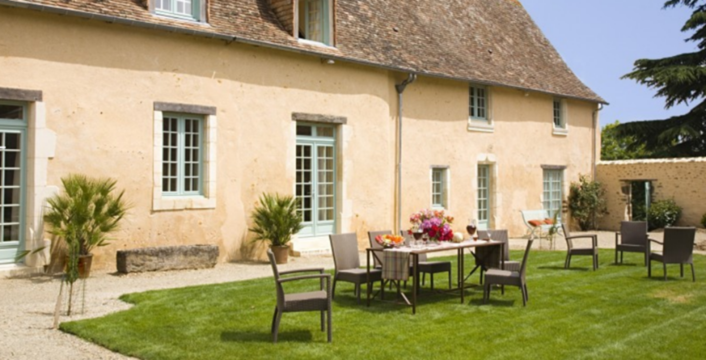 A large lawn in front of a house at Château de Saint Frambault.