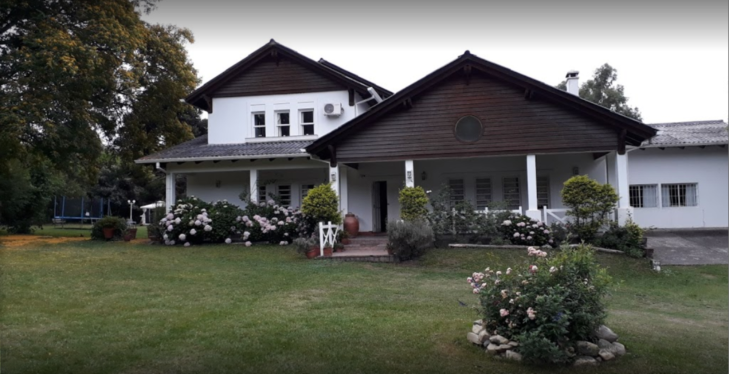 A large lawn in front of a house at Aires de San Lorenzo.