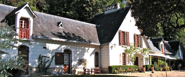 A house with trees in front of a brick building at Chambre d'hôtes et Gîtes en bord de Loire.