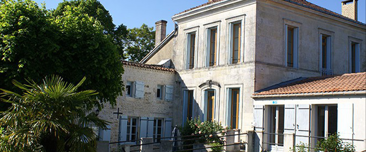 A house with trees in front of a building at Domaine la Fontaine.