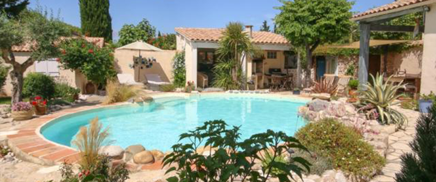 A house with a pool in front of a building at La Bergerie de Laval.