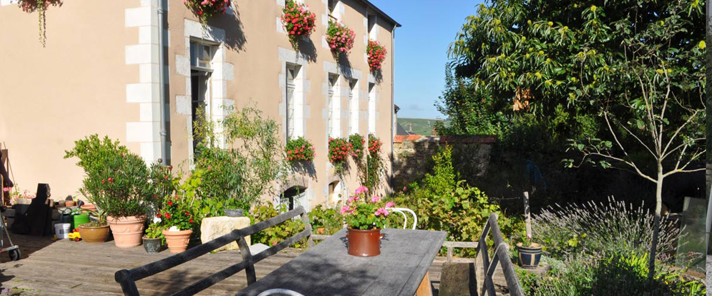 A vase of flowers sits on a bench in front of a building at Le Cep en Sancerrois.