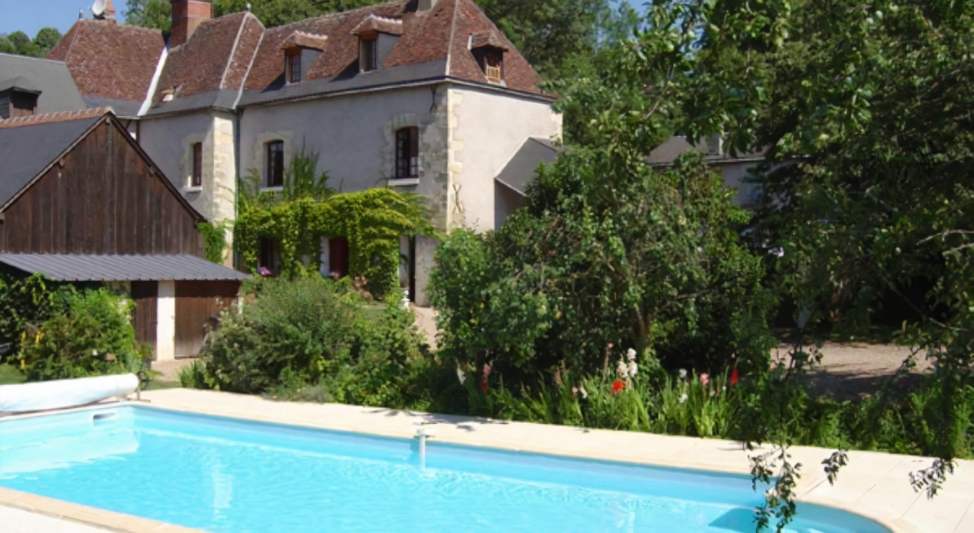 A house with a pool in front of a building at The Le Moulin des landes.