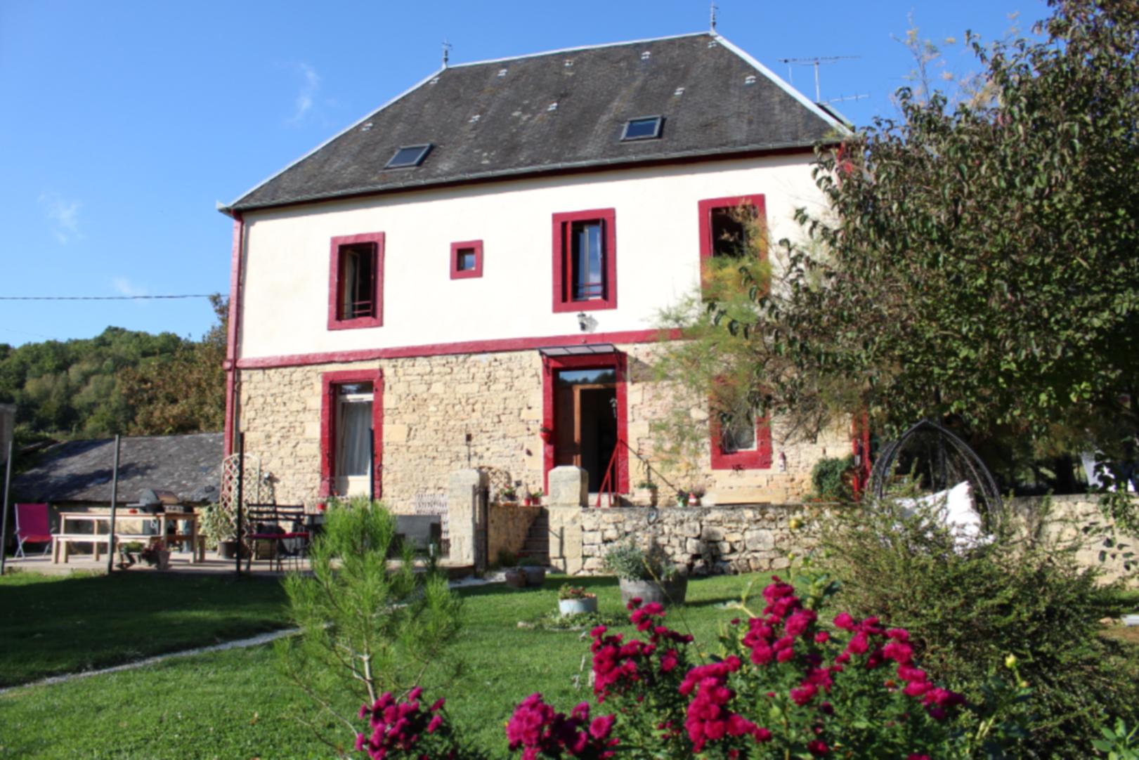 A close up of a flower garden in front of a house at La Maison Du Bonheur.