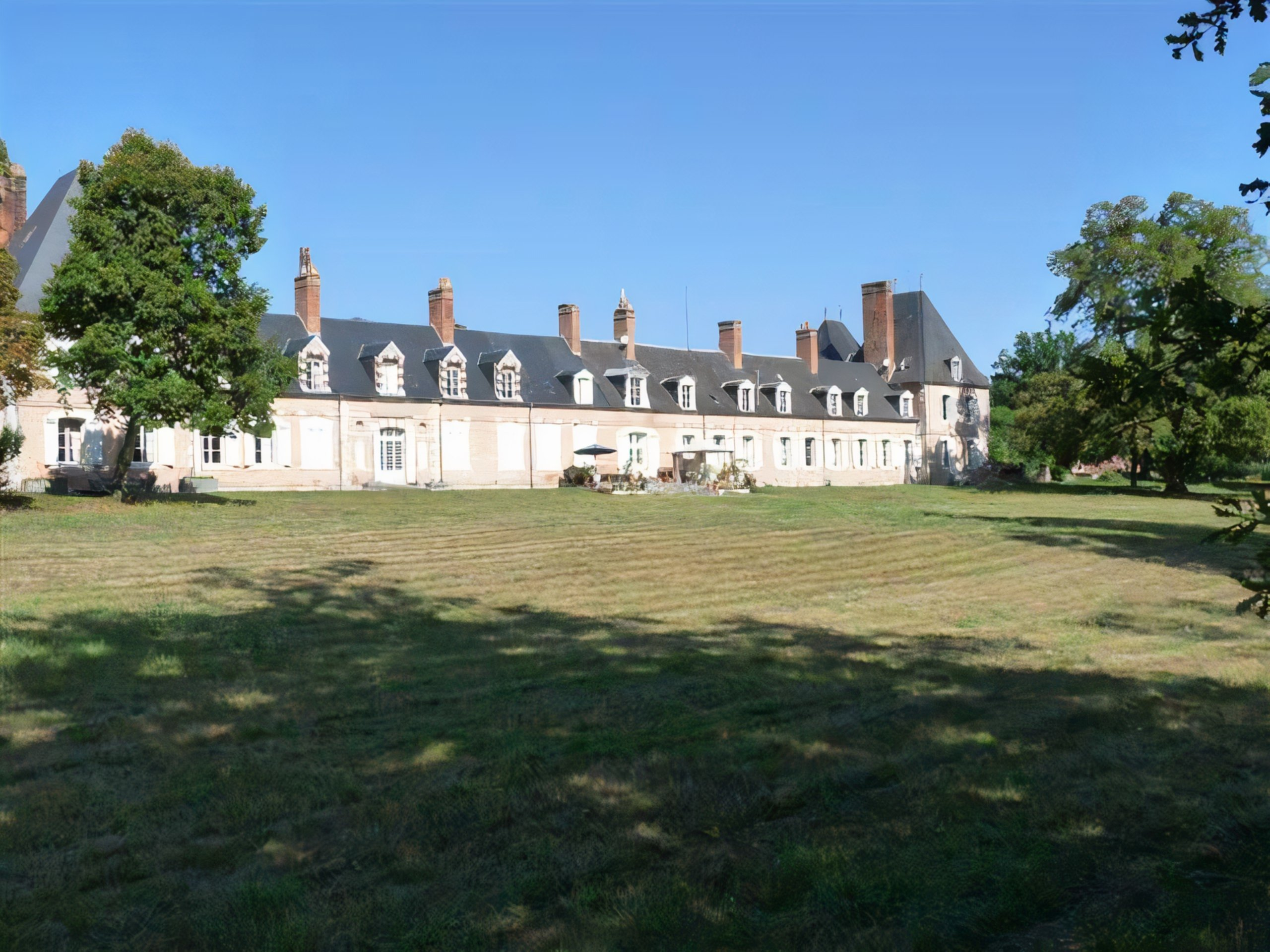 A castle on top of a grass covered field at Chateau-Brinon.