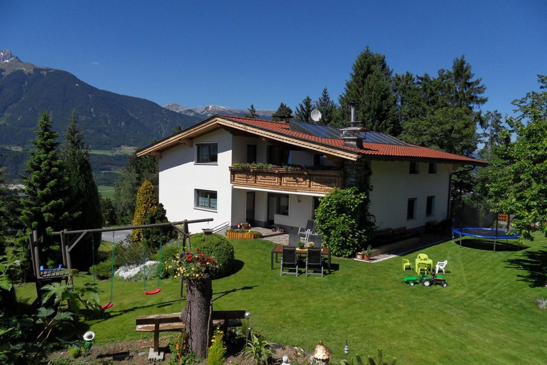 A house with a mountain in the background at Guesthouse Anfang.