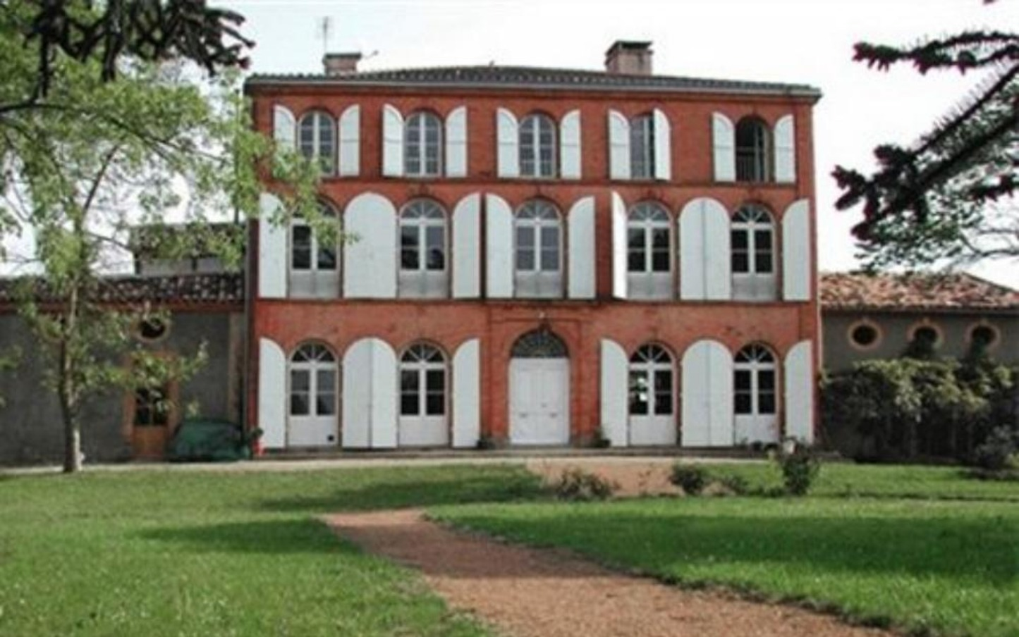 A large brick building with grass in front of a house at Au Chateau.