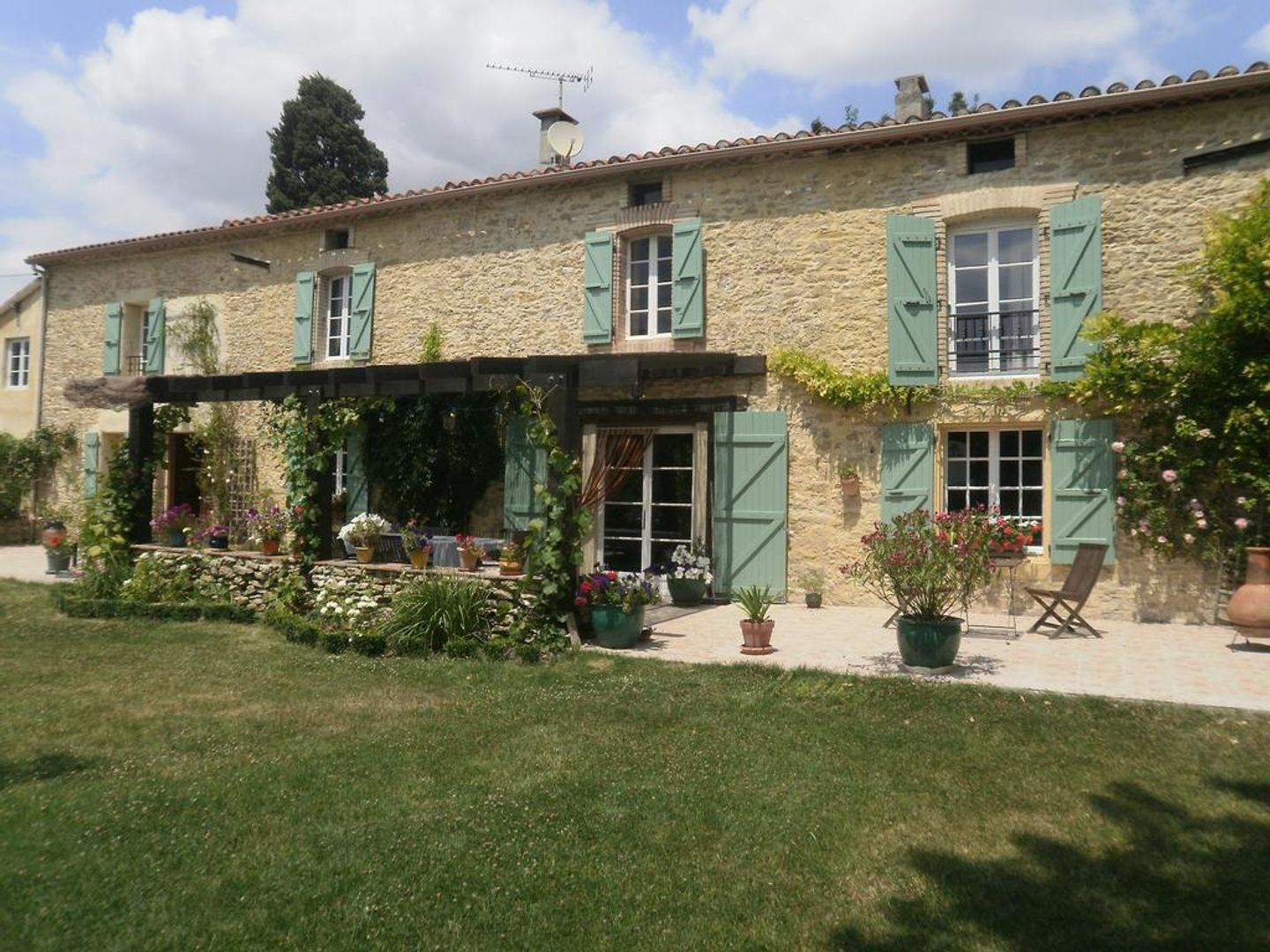 A large brick building with grass in front of a house at Domaine de Laspeyrisses.