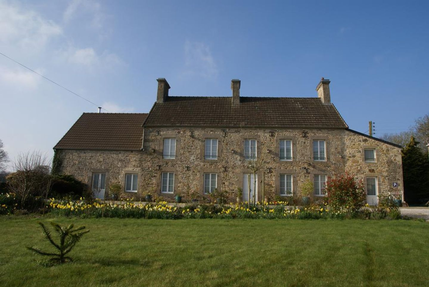 A large brick building with grass in front of a house with brice house in the background at Chambres d'hôtes La Laiterie.