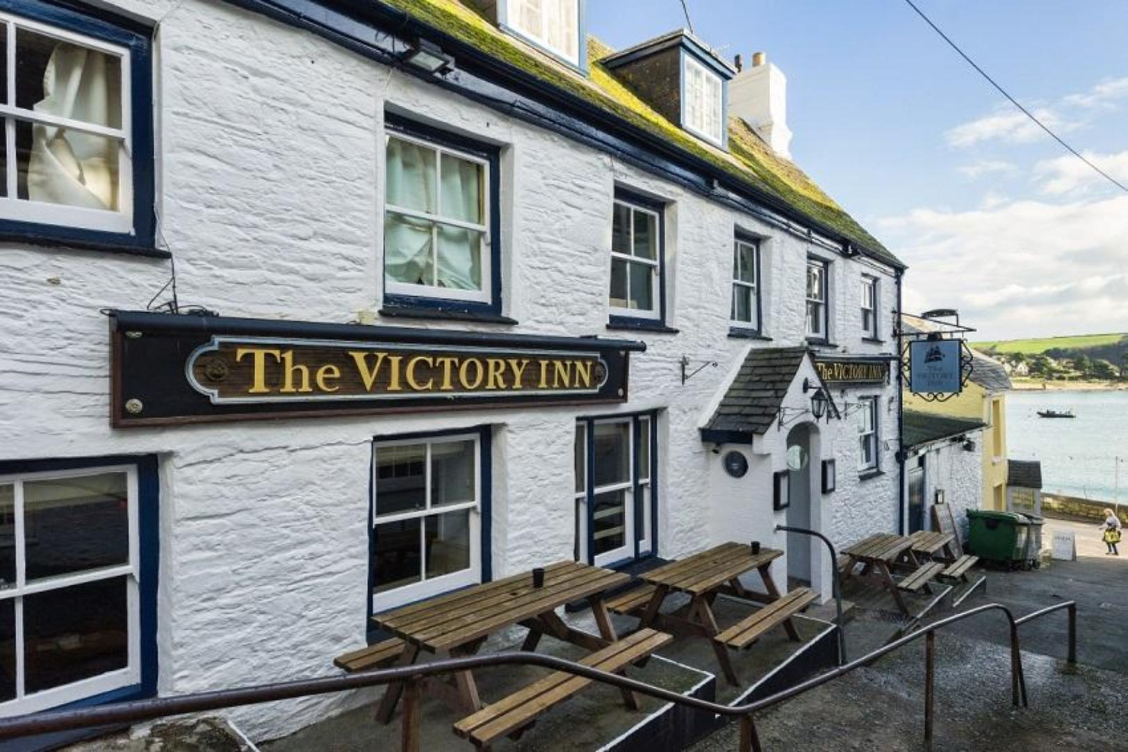 A house that has a sign on the side of a building at The Victory Inn.