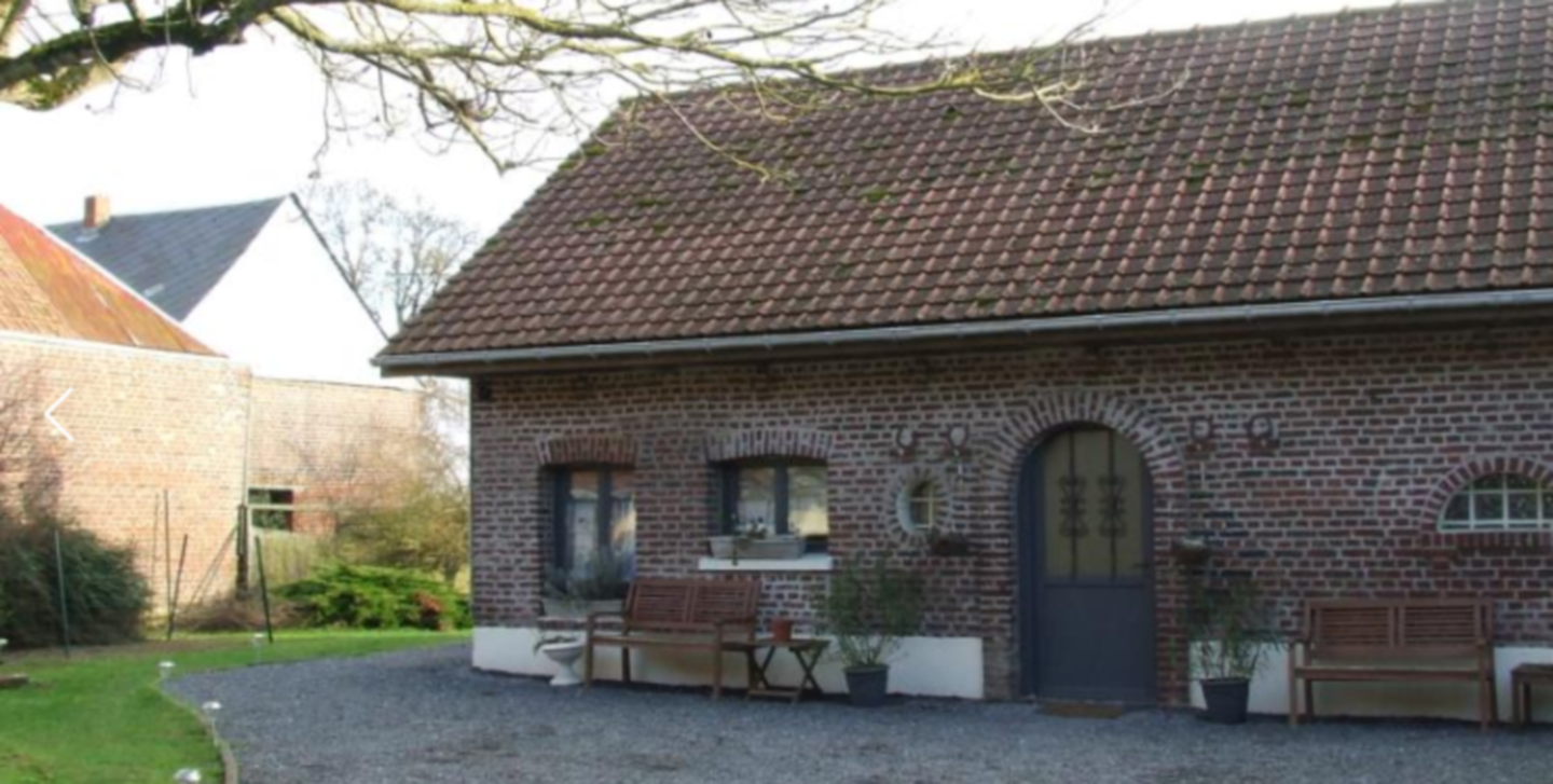 A large brick building with grass in front of a house at  L'Amartinierre.