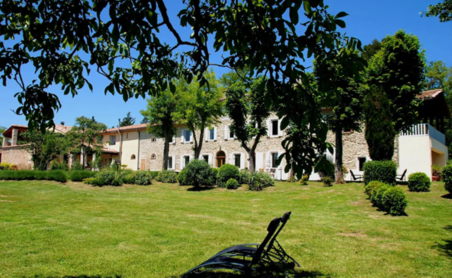 A large lawn in front of a house at Domaine La Monèze Basse.
