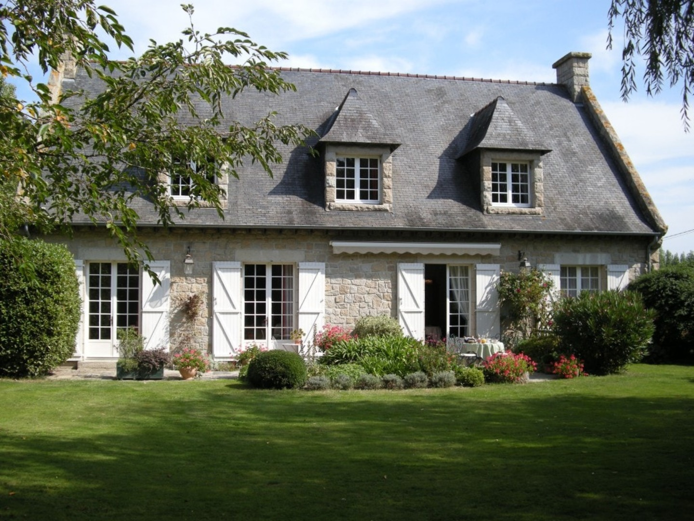 A large brick building with grass in front of a house at La Petite Ville Mallet Chambre d'hôtes de charme.