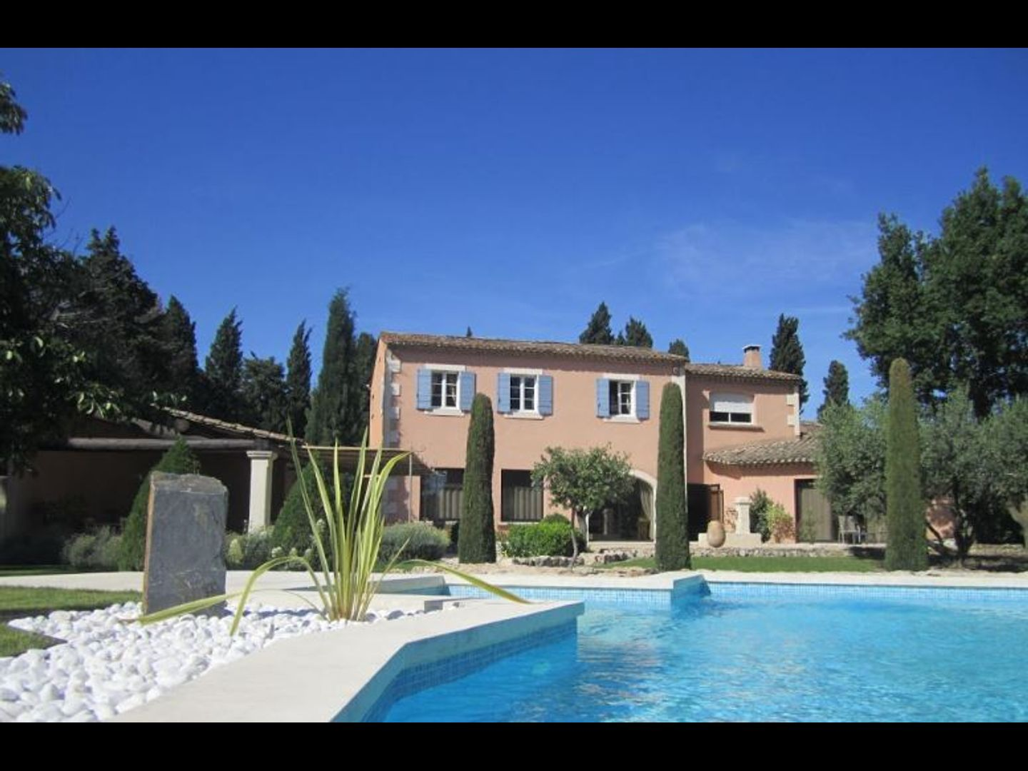 A group of palm trees with a building in the background at Le Clos Des Cyprès.