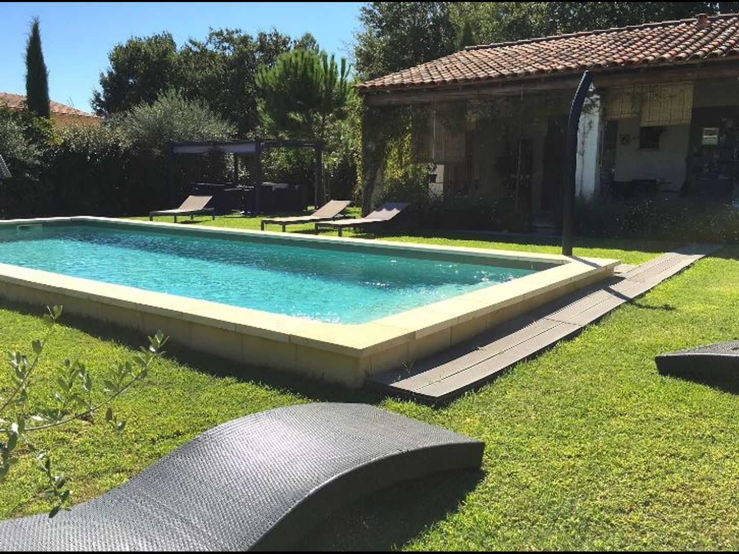 A large lawn in front of a pool at Le Jardin de Lau.