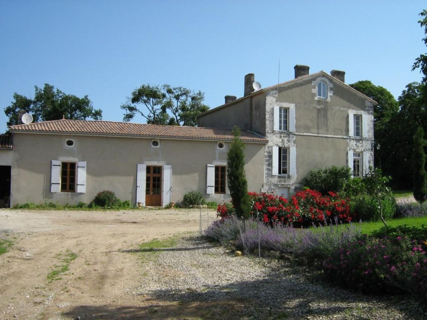A house with bushes in front of a brick building at Domaine les Galards.