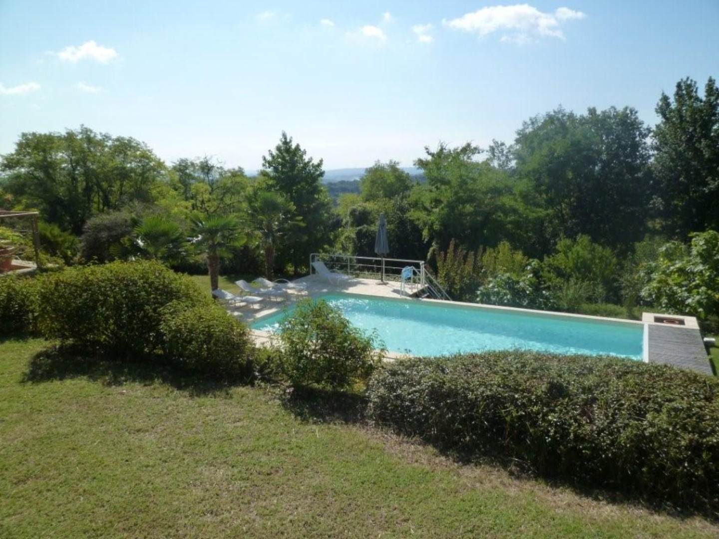 A garden with water in the background at Les Hauts de La Faurie.