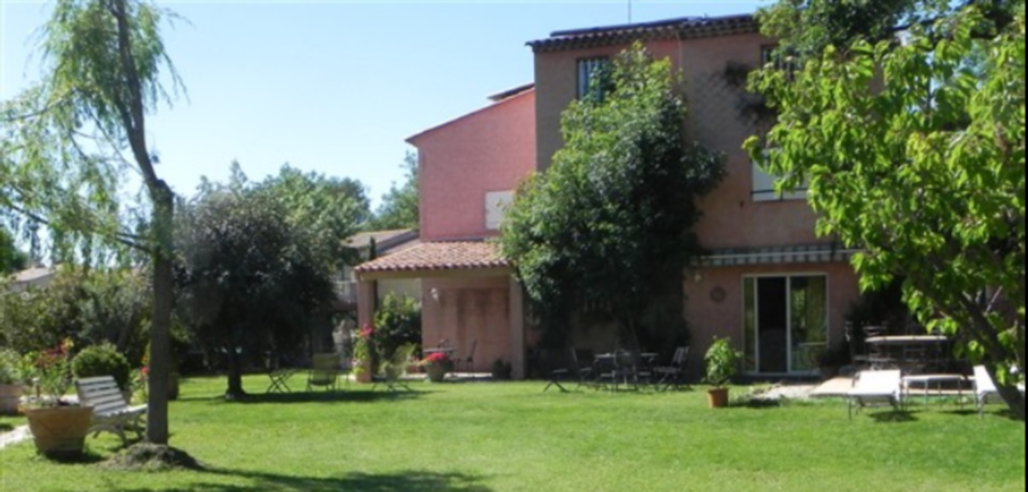 A large lawn in front of a house at B&B Le Clos des Vignes.