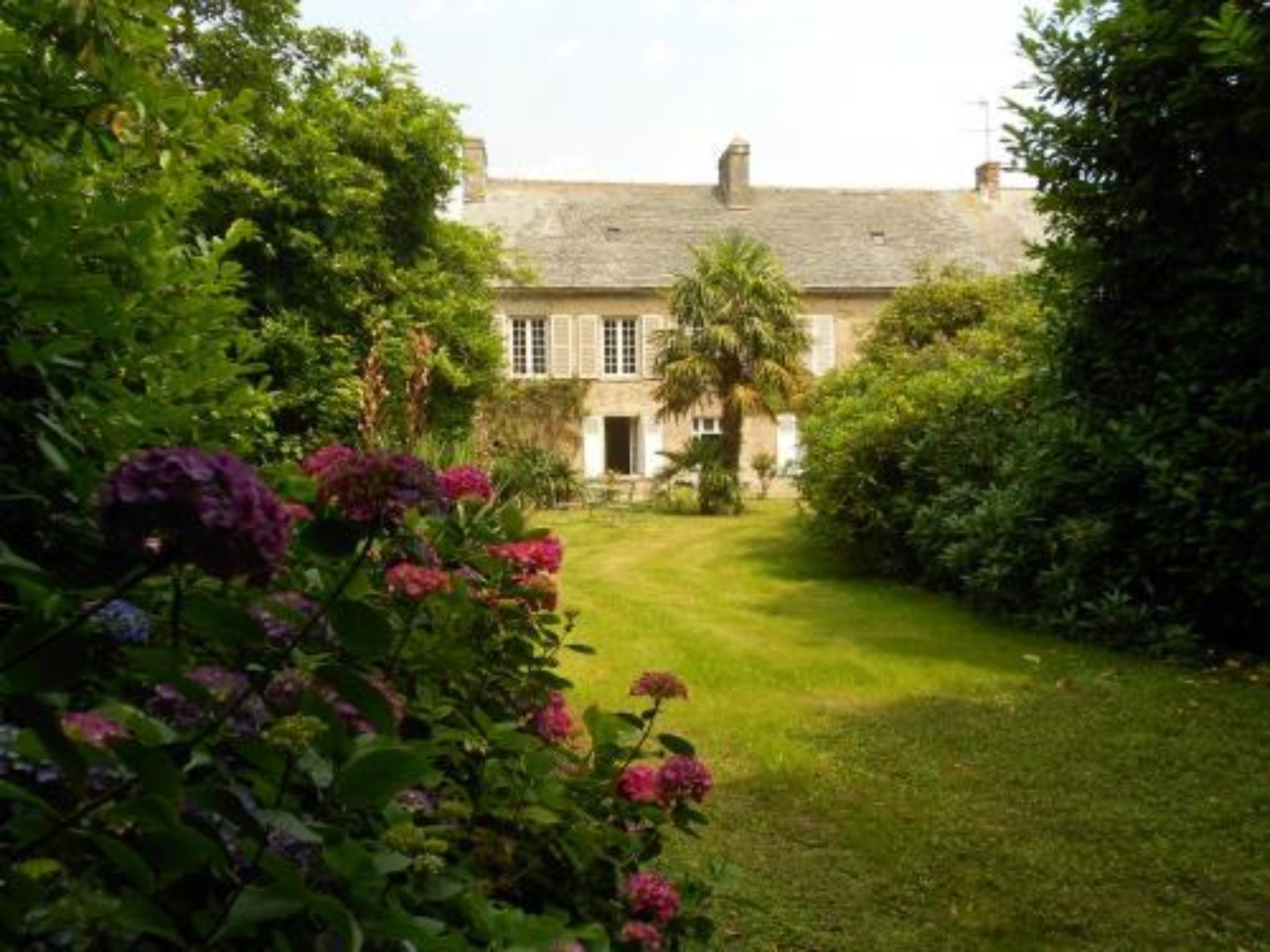 A house with bushes in the background at Manoir de Bellauney.