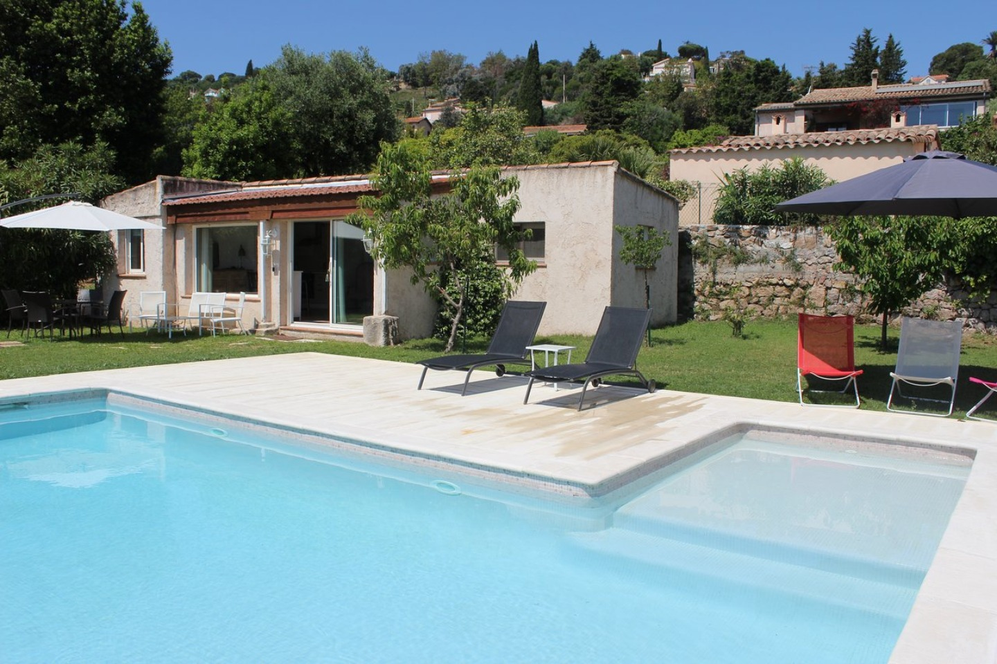 A house with a pool in front of a building at La Bastide Au Soleil.
