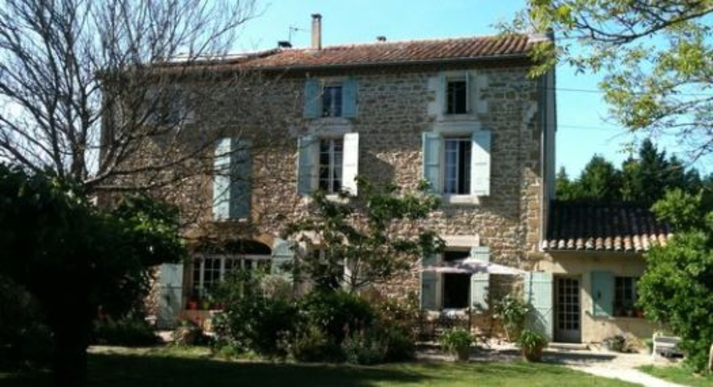 A house with trees in front of a brick building at Le mas des avettes.