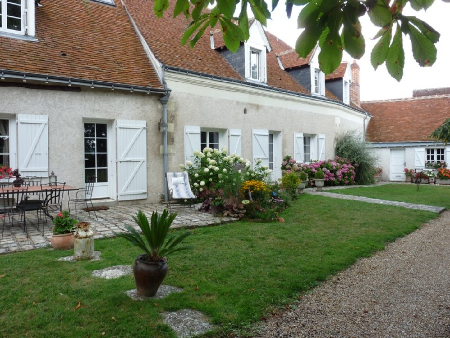 A large lawn in front of a house at AUX REFLETS DU CHER.